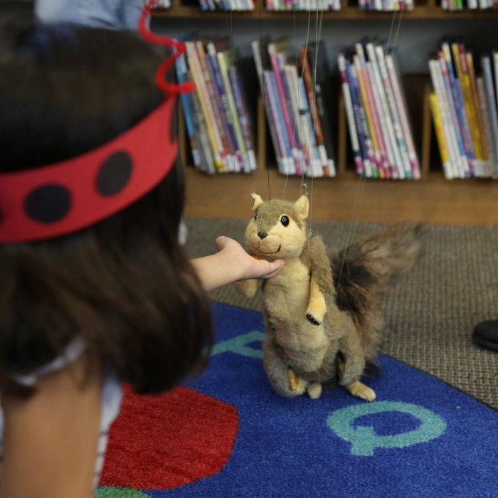 A young child interacts with a squirrel puppet at a Nature Day event.